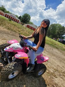 An image of Desiree Renteria riding a quad she is an employee at Elevated Dispensary